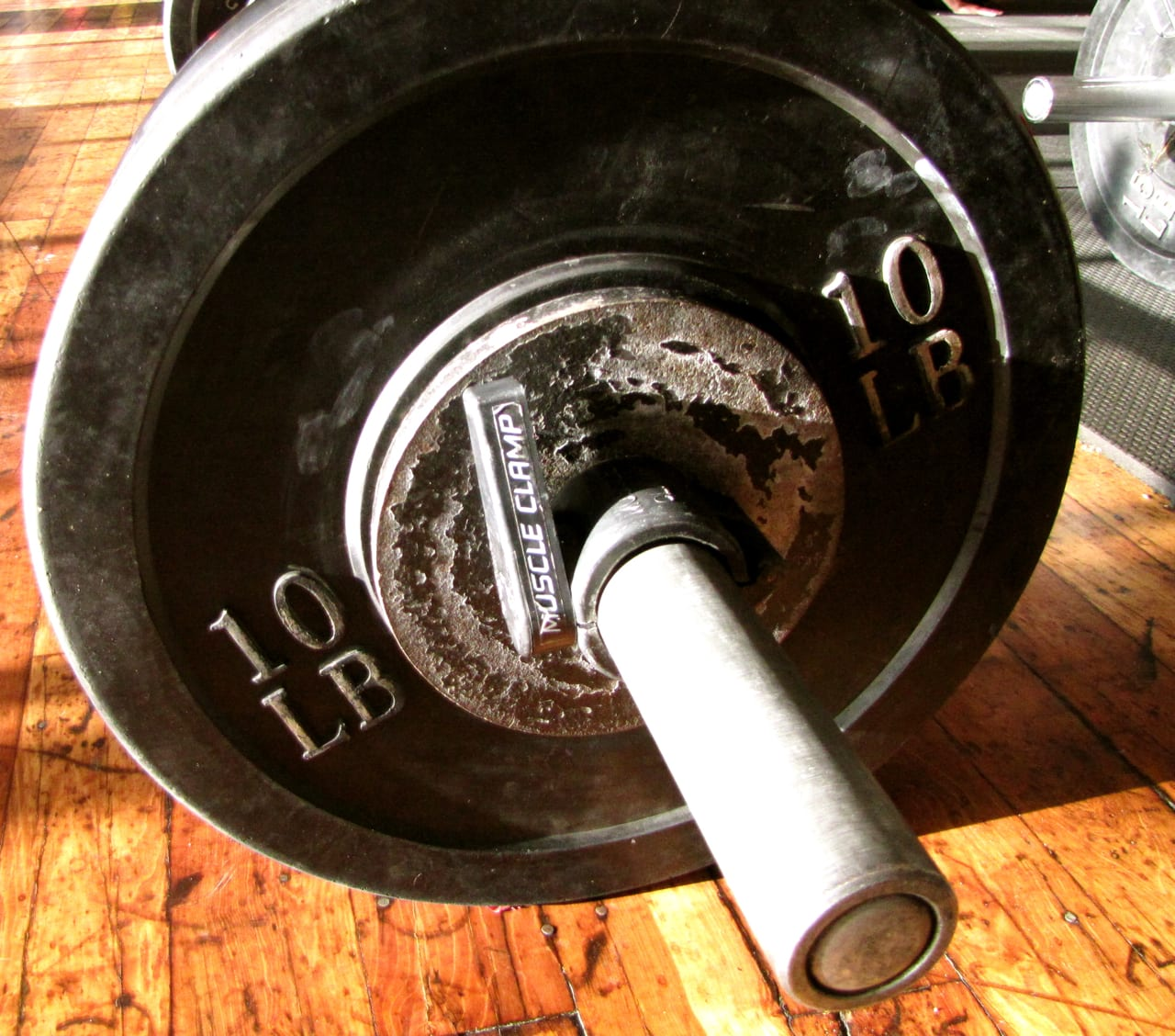 barbell with plates on wooden floor