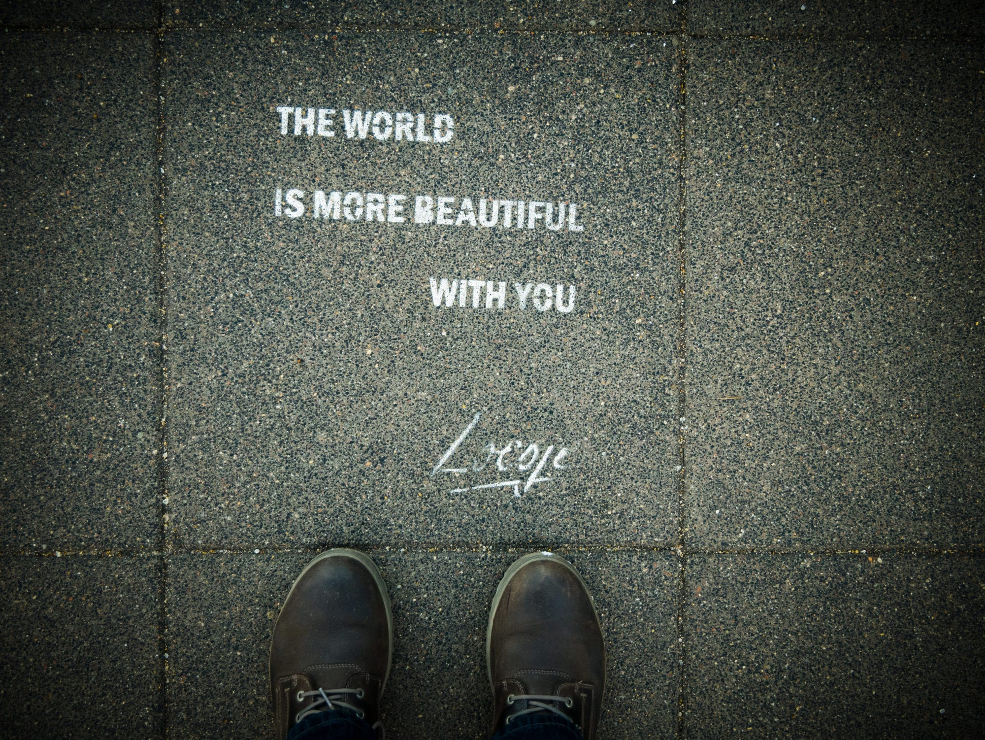 words written on pavement the world is more beautiful with you