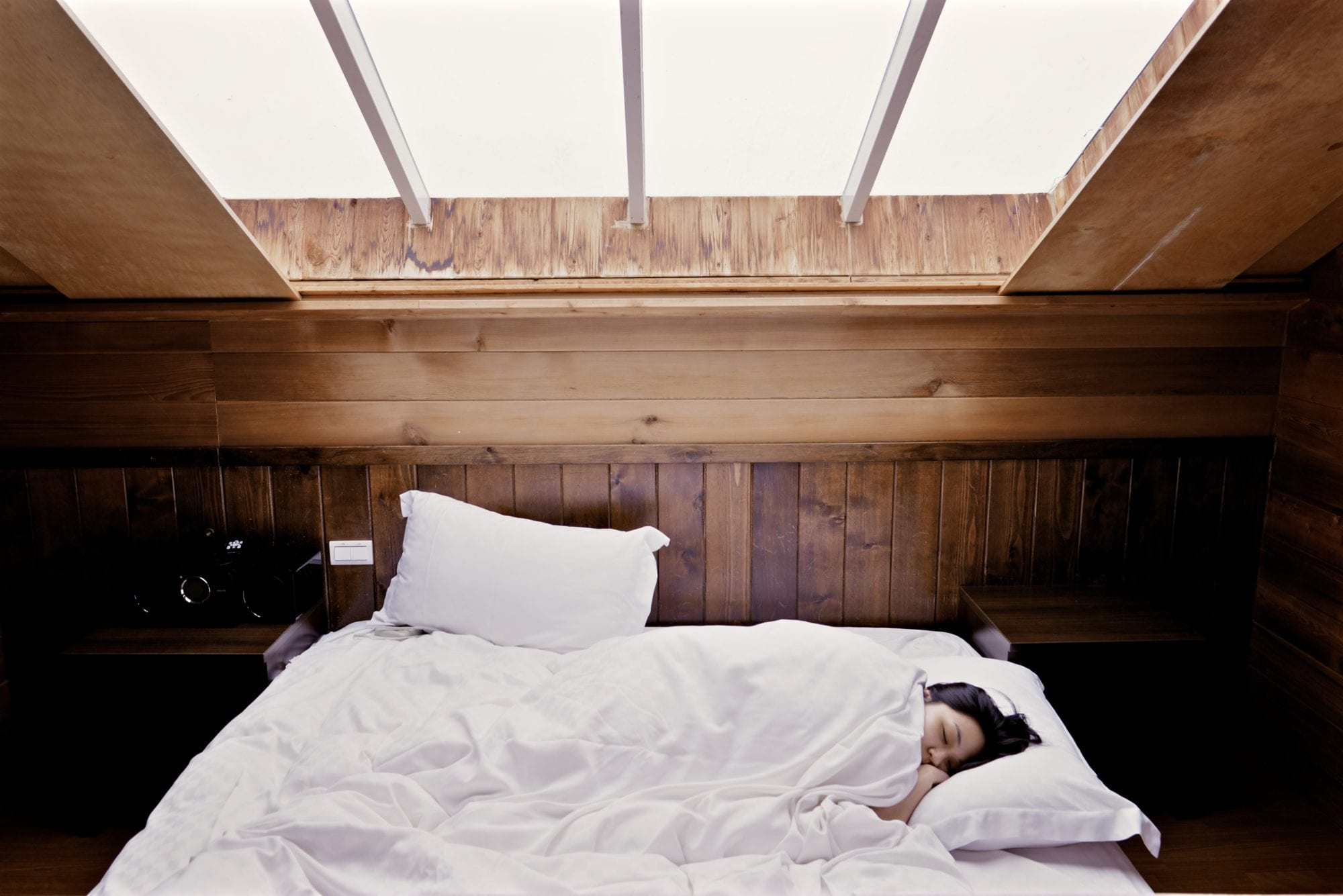 woman in bed under skylight