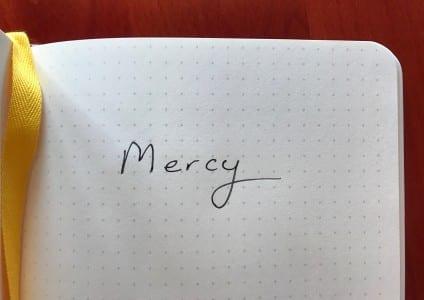 the word mercy written in pen in a notebook plus yellow ribbon