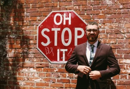 Sign oh stop it with man in suit in front of sign