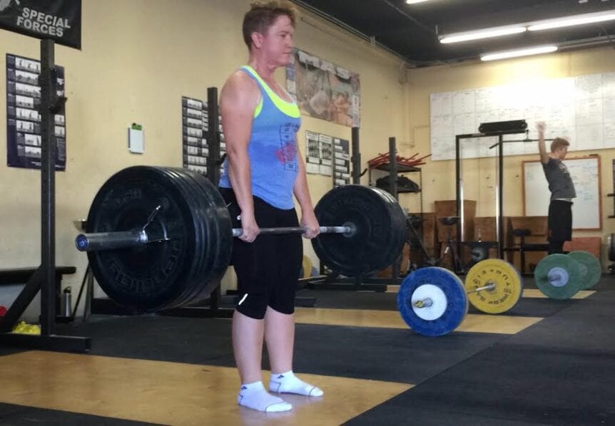 woman standing with barbell and heavy weights in her hands in a deadlift