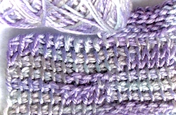 Lorna's Laces fingering weight silk yarn dyed in the same colorway. Swatch is a mix of Tunisian crochet stitches: simple, knit, and purl.
