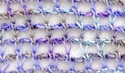 Tunisian crochet extended stitch in a simple net pattern with hand dyed sock yarn in light purples, tans, and sea blues.