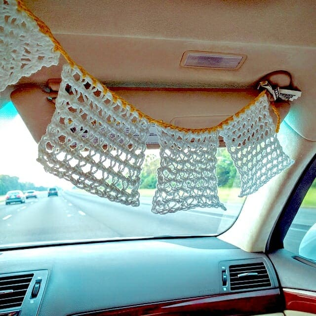 Lacy Tunisian crochet swatches crocheted together to form a Mexican 'papel picado' style bunting. It's hung in the car during our road trip to the CGOA conference.