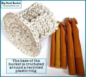 "Set of 5 sizes of jumbo wood crochet hooks, and the crocheted ""bucket"" caddy for them showing the base that's reinforced by crocheting around a recycled plastic ring."