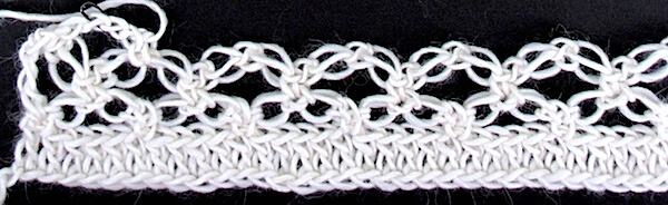 A row of love knots has been worked into a row of double crochets (an easy base). A second row of love knots is crocheted into the first row of them to create the classic lacy diamond mesh. This is a 19th cen. stitch pattern.