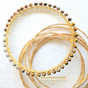 A slim gold bangle is covered with gold wire crochet and metal beads.