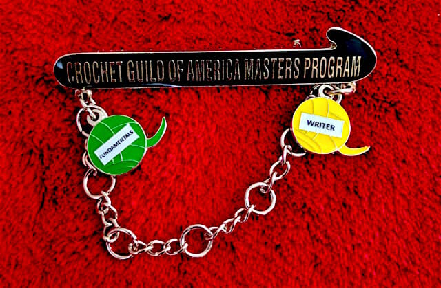 The new CGOA Master's Program pin. I've earned two charms so far: Writer, and Fundamentals (because I wrote a few chapters of it).