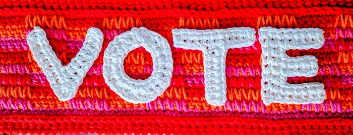Crocheted letters V-O-T-E against sunrise-colored crochet background