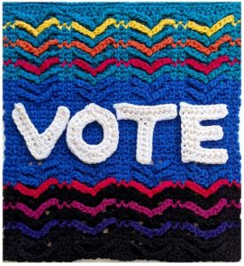 Tunisian crochet letters spell V-O-T-E against a rainbow aran crochet background.