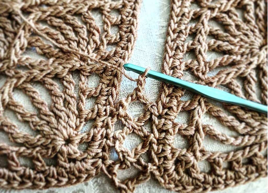 Close up of seam that joins two crochet motifs with stitch equivalents: linked bent tall stitches match chains and slip stitches.