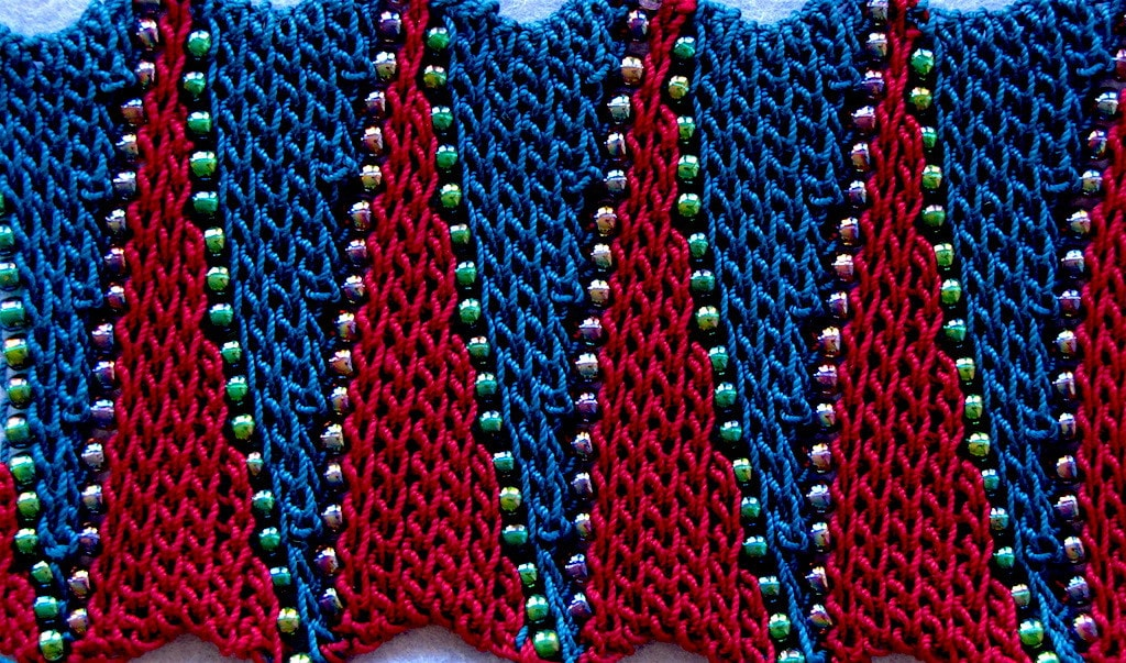 Pattern of short row wedges in alternating colors separated by beads shown flat