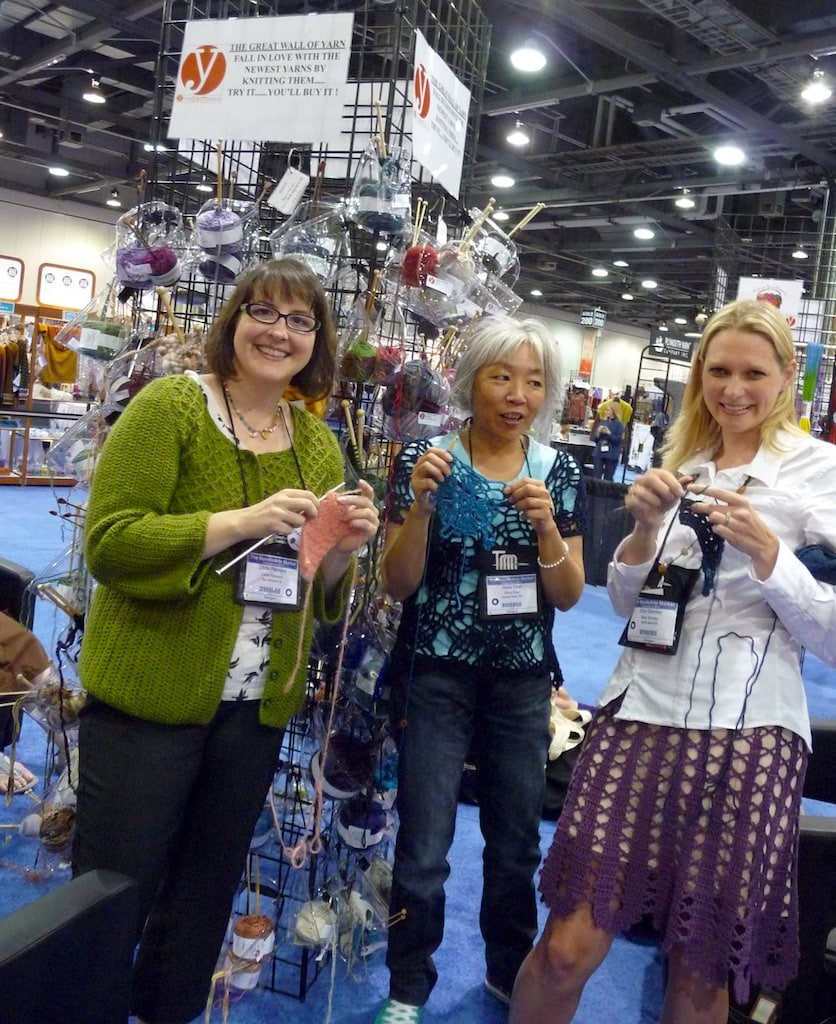 Linda Permann, Doris Chan, and Ellen Gormley using new season's yarns on the yarn wall to create crochet swatches to balance out all the knitted ones.