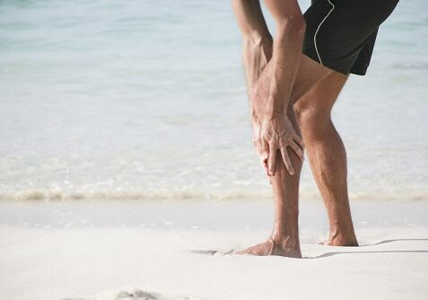 """""""A male person, having severe  pain in his lower limb at the beach. This pain could be due to calf pain or to a pain in the shin, the so called shin splint syndrome. XXL size image."""""""