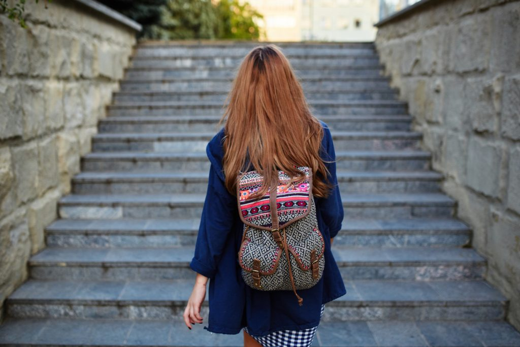 Student girl with a backpack climbing stairs. Rear view