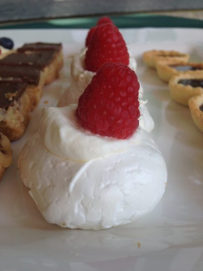 Mini Pavlovas with whipped cream and raspberries