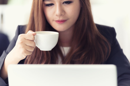 45314162 - asia young business woman sitting in a cafe with laptop and coffee, business concept