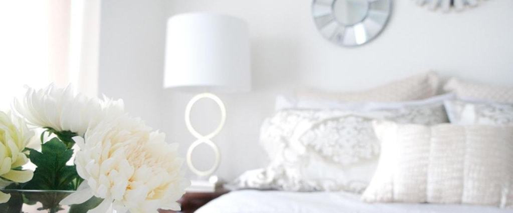 Fresh flowers with layers of textured pillows in a light palette bedroom