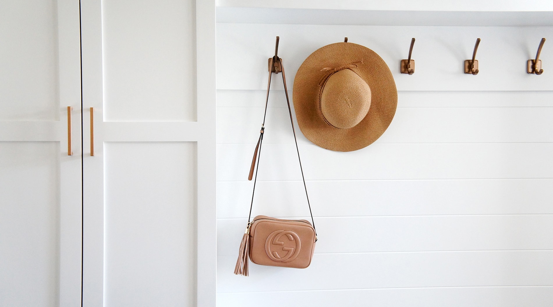 A series of hooks are mounted over shiplap, which expands the width and adds a timeless texture