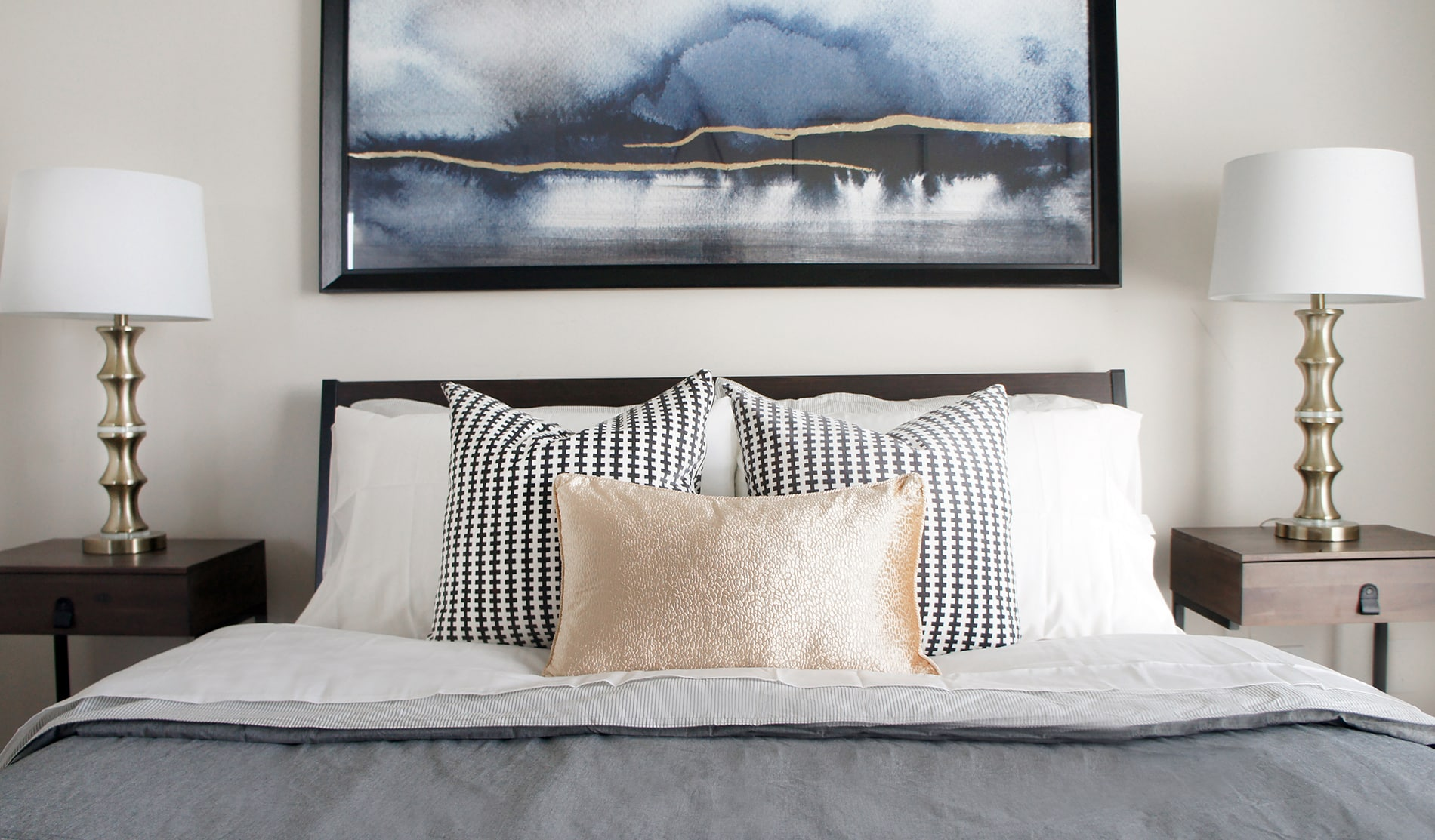 A piece of wall art featuring blue and gold added visual interest and height over the headboard in one of the condo bedroom designs