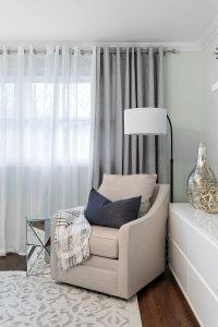 Dramatic full-length drapes behind a cozy reading chair