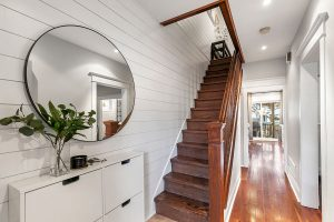 The shiplap runs all the way up along the staircase wall and into the upstairs hallway