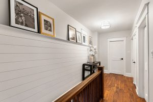 The shiplap in the upstairs hallway creates a shelf for family photos
