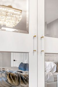 A shimmery chandelier behind glass-panelled bedroom double doors