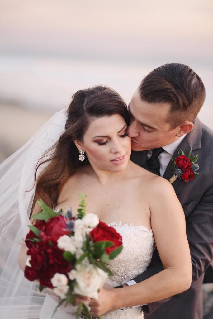 bride and groom on beach, burgendy wedding flowers