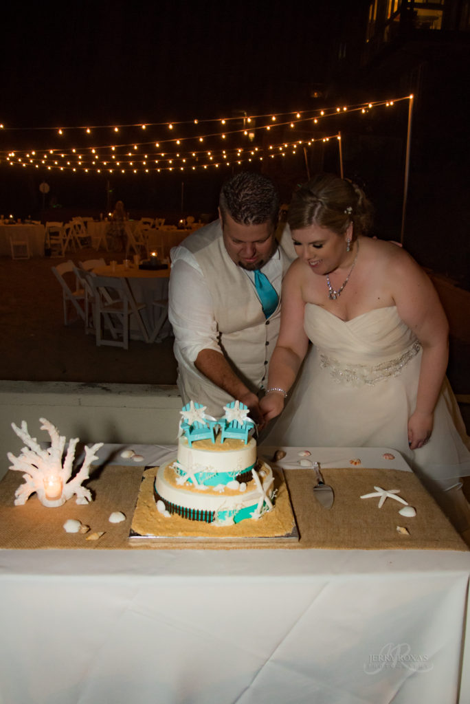 beach themed wedding cake, bride and groom cutting cake