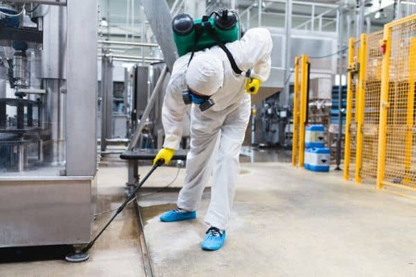 commercial pest control technician spraying under machine in philadelphia factory