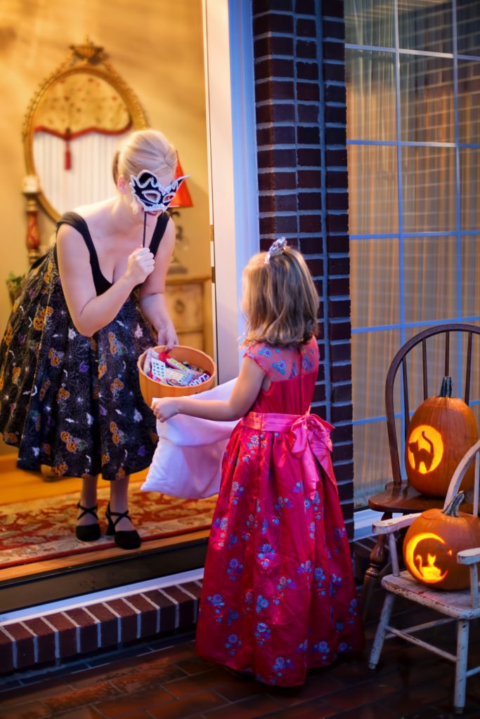 Woman gives candy to a young trick or treater