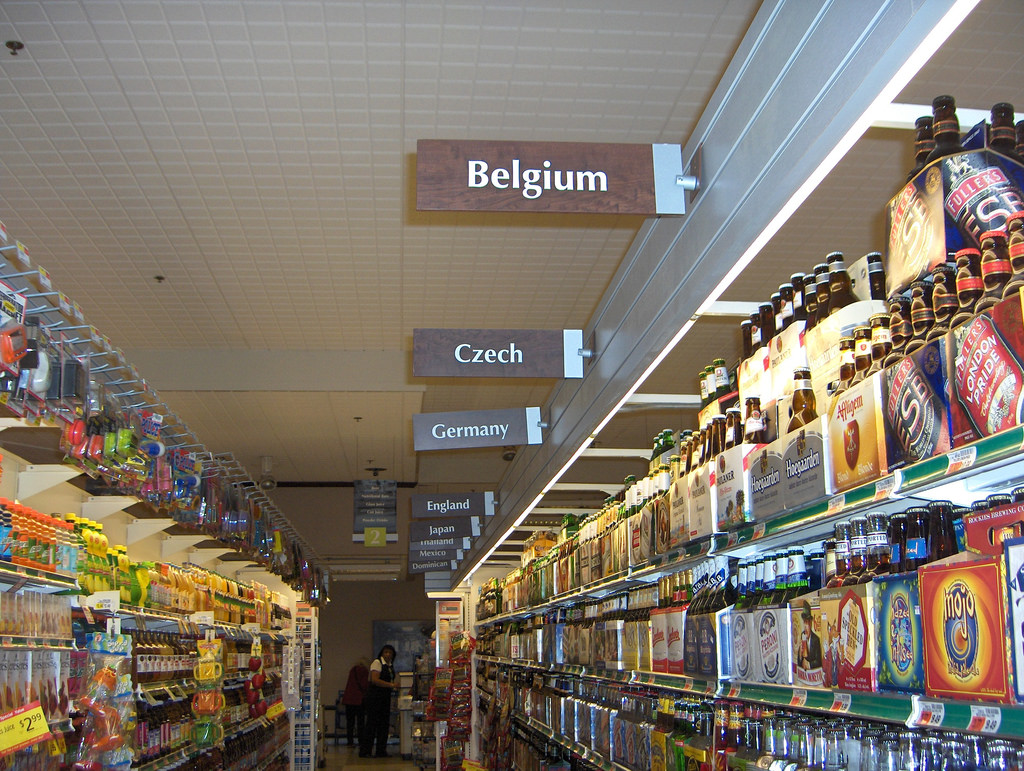 Craft beer aisles in a grocery store. Each aisle is labeled with the name of a different country.
