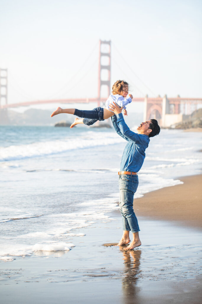 dad playing with daughter at the beach