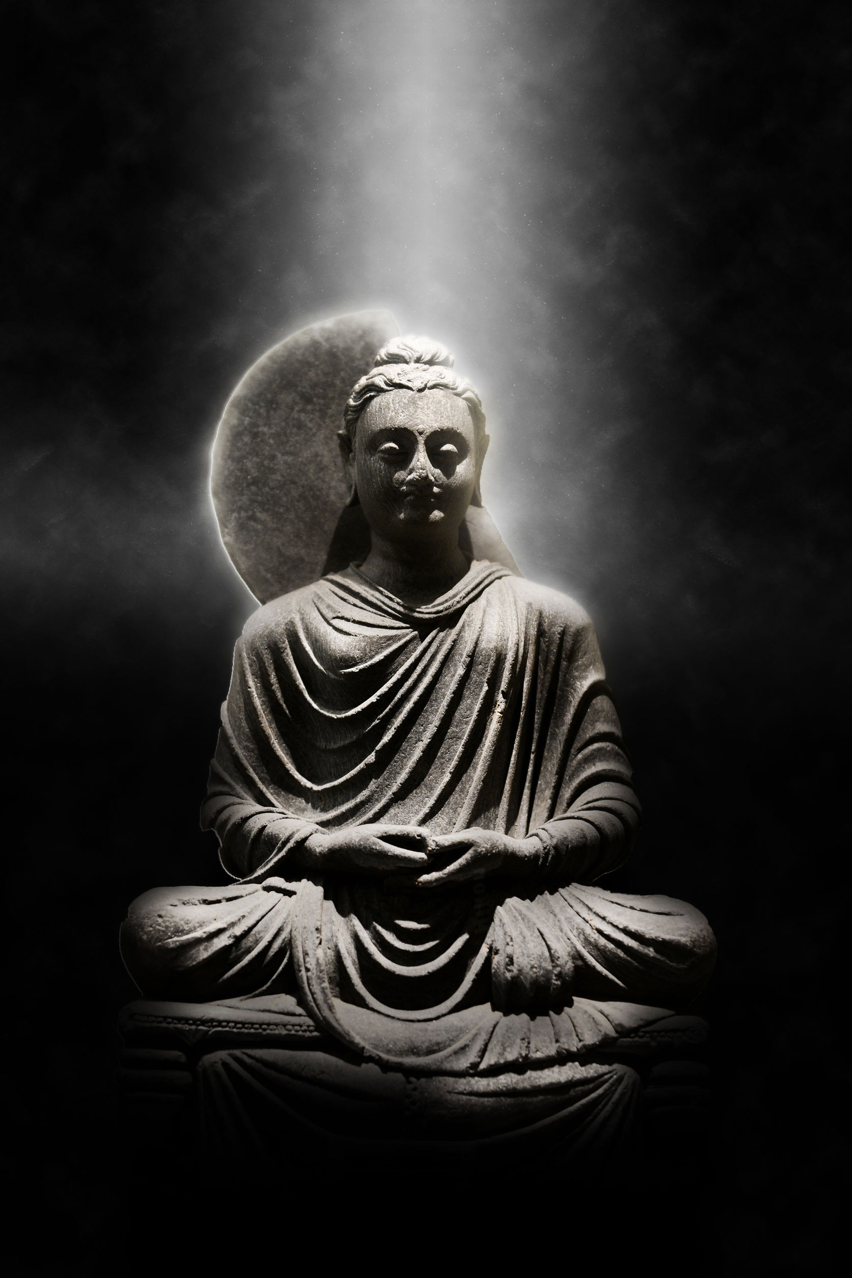 41026822 - full length stone carved seated buddha statue dramatically lit from above on dark background, meditation and spirituality concept still life image