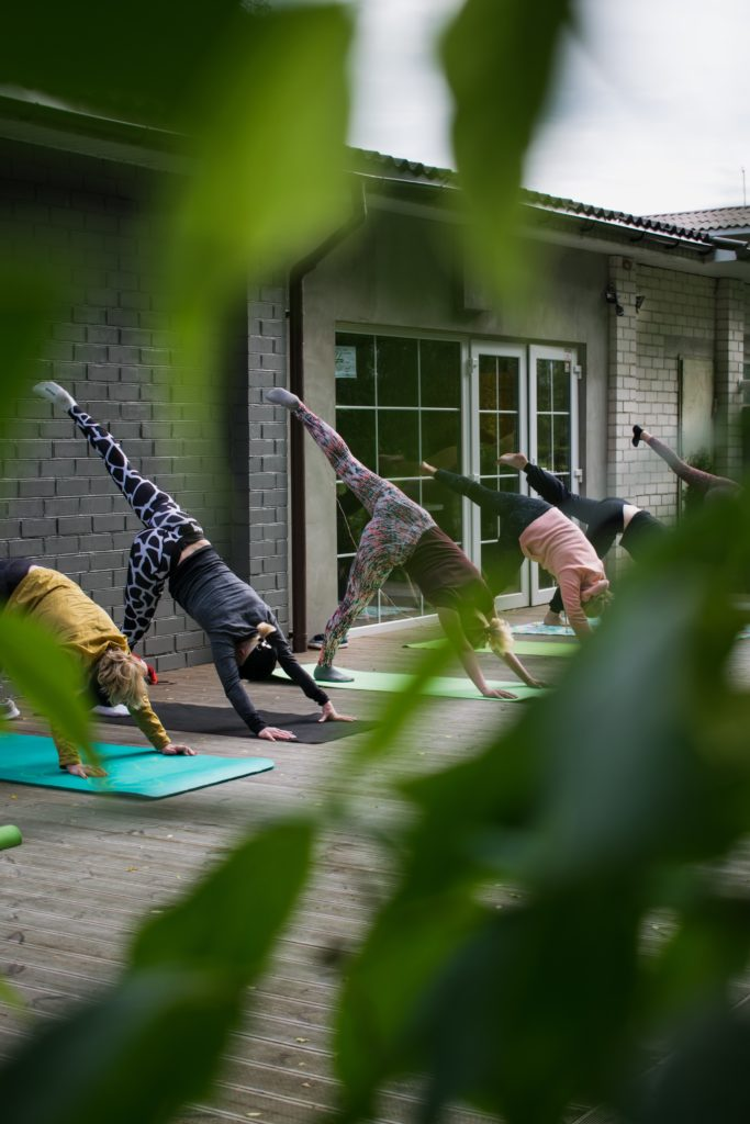 three women doing yoga on mats holistic recovery path