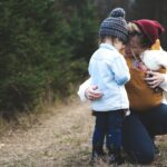 mom hugging young children crouched down in winter met professional interventionist