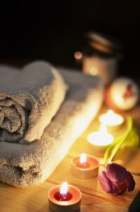 white folded towel with candles glowing meditation and recovery
