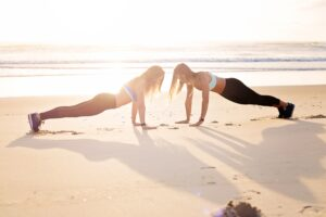 two woman on beach yoga recovery coaching for addiction