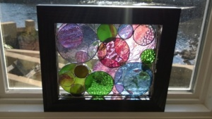 my 2 stained glass circles projects layered with the morning sun coming through