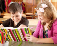Boy and Girl Reading a Book Together