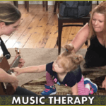 Noel Anderson of Anderson Music Therapy plays guitar for a child and her mother during a group music therapy session at the Sanctuary.