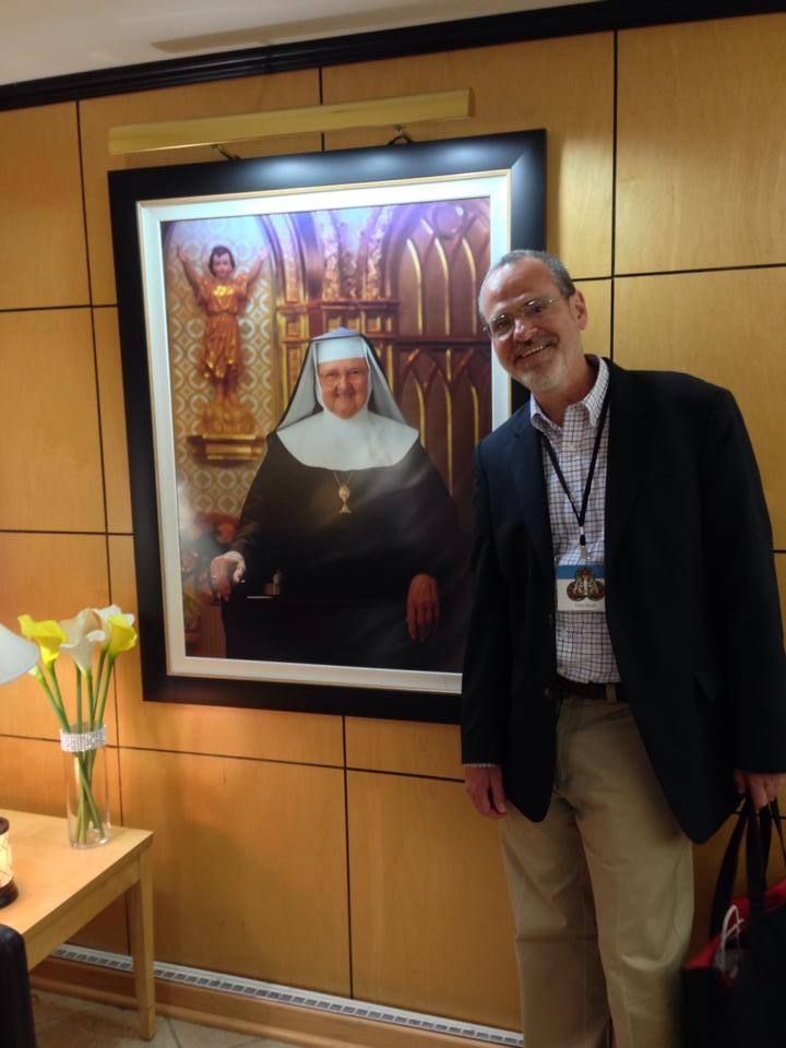 Catholic speaker and author Gary Zimak posing next to a portrait of Mother Angelica at EWTN