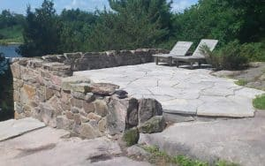 Stone patio at lake edge with retaining wall
