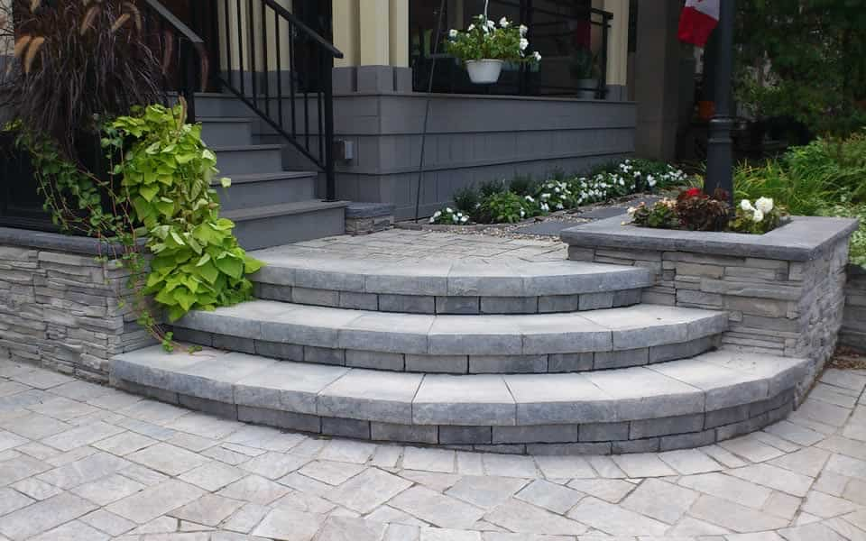 Curved front step with retaining walls design by Rhonda Derue installation by Yards Unlimited Landscaping Inc.
