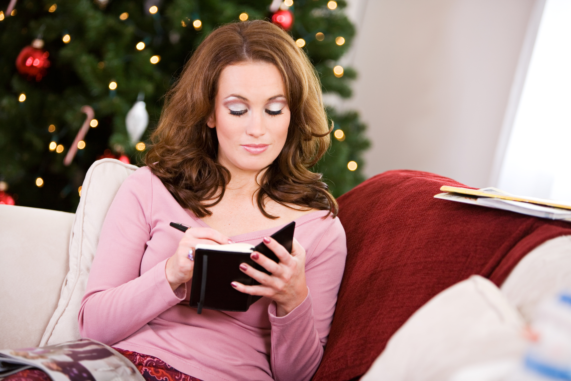woman writing with a Christmas tree behind her