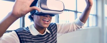 Smiling young African American woman with VR glasses reaching out and learning new technology in a trendy warehouse office loft