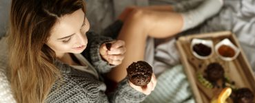 Woman eating muffin cupcake in bed