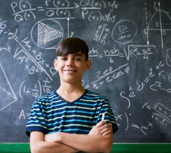 Concept on blackboard at school. Young people, student and pupil in classroom. Smart hispanic boy writing math formula on board during lesson. Portrait of male child smiling, looking at camera